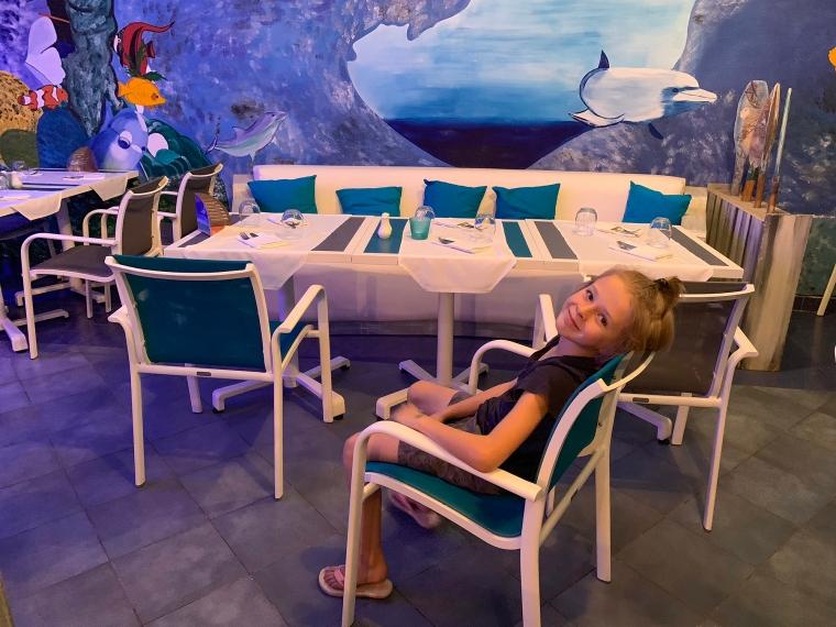Ett dukatbord med en väggmålning bakom, föreställande en undervattensvärld med fiskar.