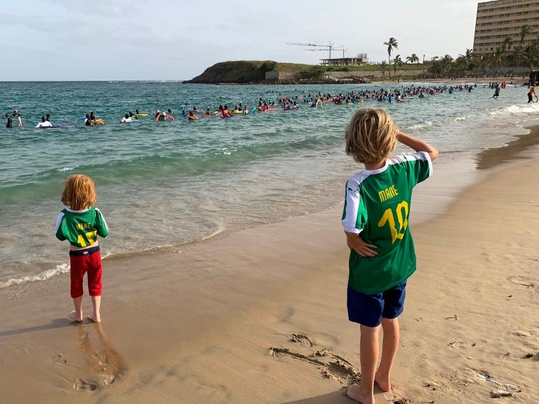 Två barn tittar på människor i vattnet som gymnastiserar.