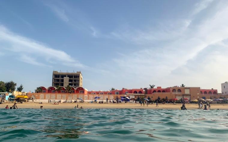 Bild tagen från havet in mot en strand med byggnader.
