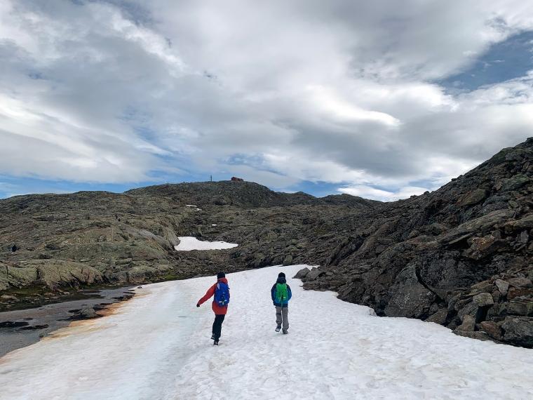 Två barn går på snö på ett berg.