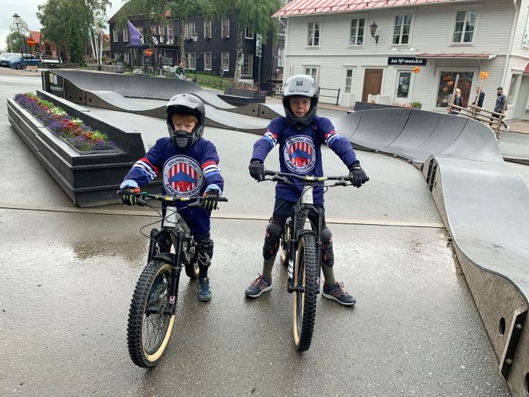 Två barn står med skydd och hjälm och var sin downhillcykel.