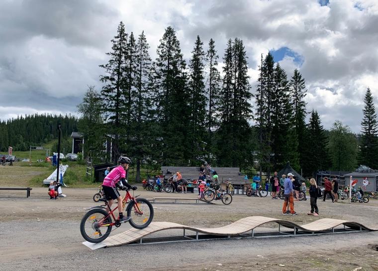 Ett barn cyklar på ett hinder.