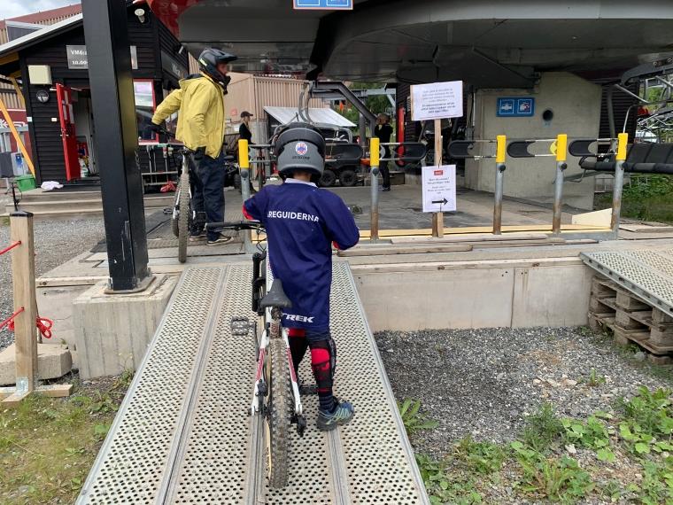 Ett barn står och väntar med sin cykel.