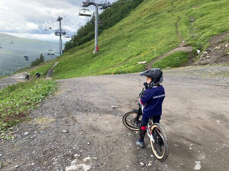 Ett barn står och väntar med sin cykel i toppen av en backe.