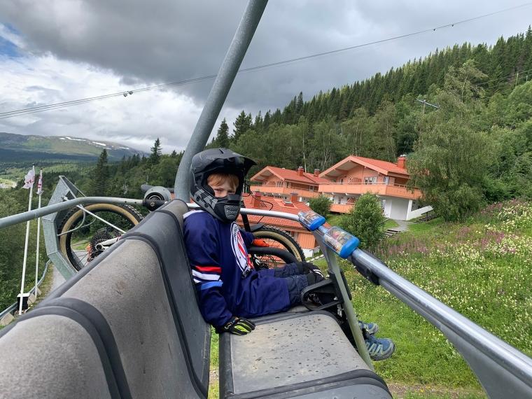 Ett barn med cykelutrustning i en stolslift.