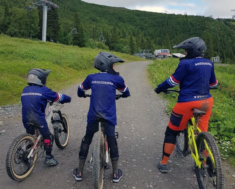 En vuxen och två barn står beredd med sina cyklar.