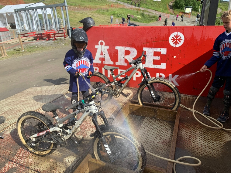 Två barn sprutar vatten på sina cyklar.