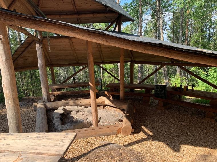 Bänkar och bord och en eldstad under ett tak. Allt byggt i trä.