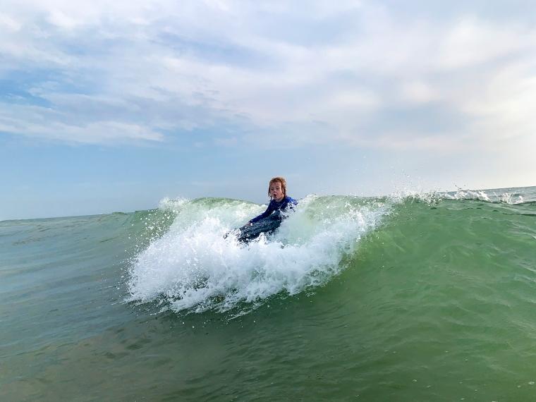 Barn som surfar på en våg.
