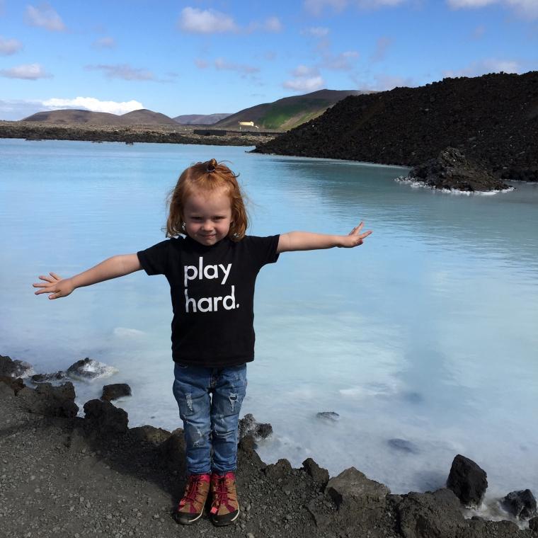 Ett barn står med utsträckta armar framför blått vatten.