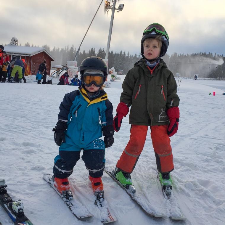 Två barn står på slalomskidor i en backe.