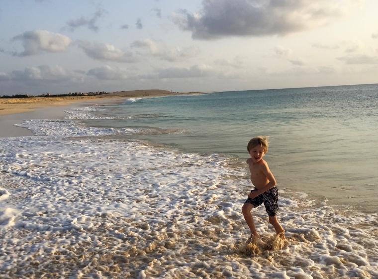 Ett barn i badbyxor springer i vattenbrynet.