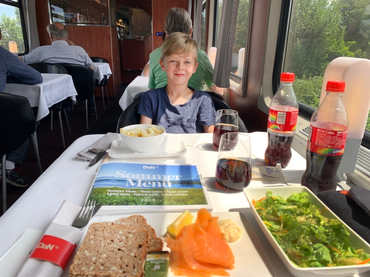 Ett barn sitter i en restaurangvagn med middag framför sig.