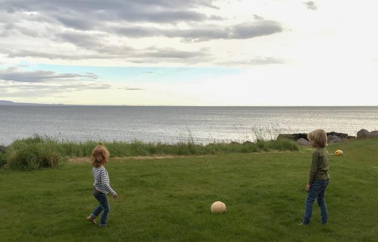 Två barn spelar fotboll på en gräsmatta med havet i bakgrunden.