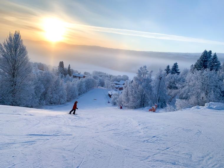 Ett barn åker snowboard i en öde backe i solnedgång.