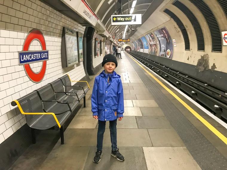 Ett barn står på perrongen i tunnelbanan Lancaster Gate.
