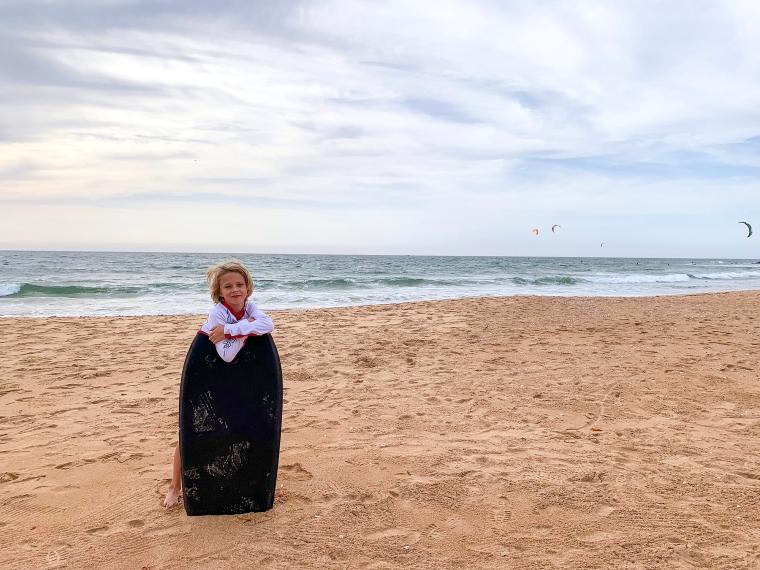 Ett barn står med en surfbräda på en strand med havet i bakgrunden.
