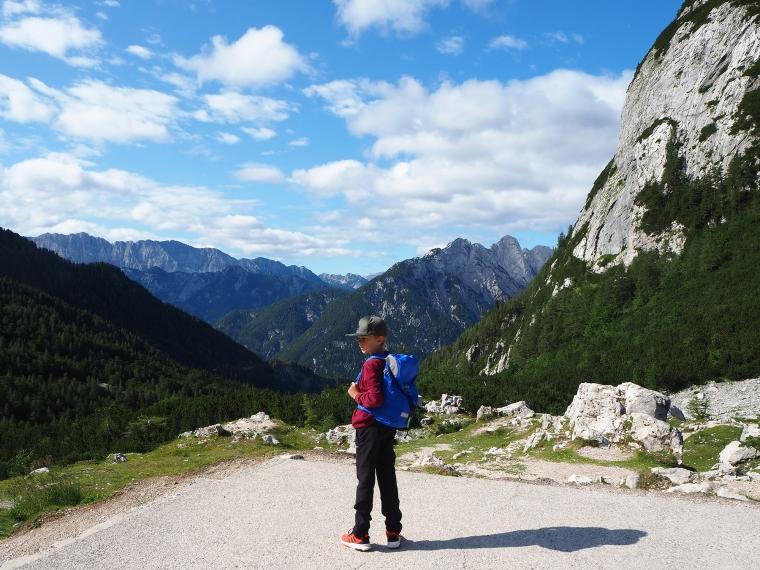 Ett barn med ryggsäck står med berg i bakgrunden.