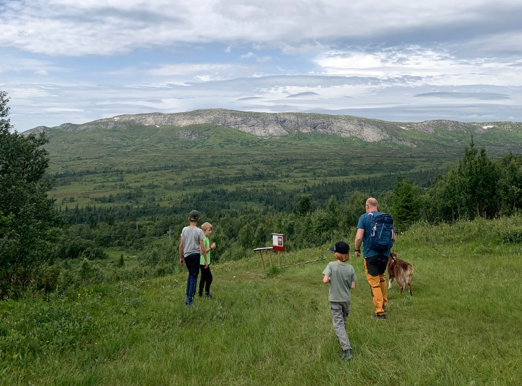 En man, en hund och trebarn står i en skidpist på sommaren men vacker utsikt över berg i bakgrunden.