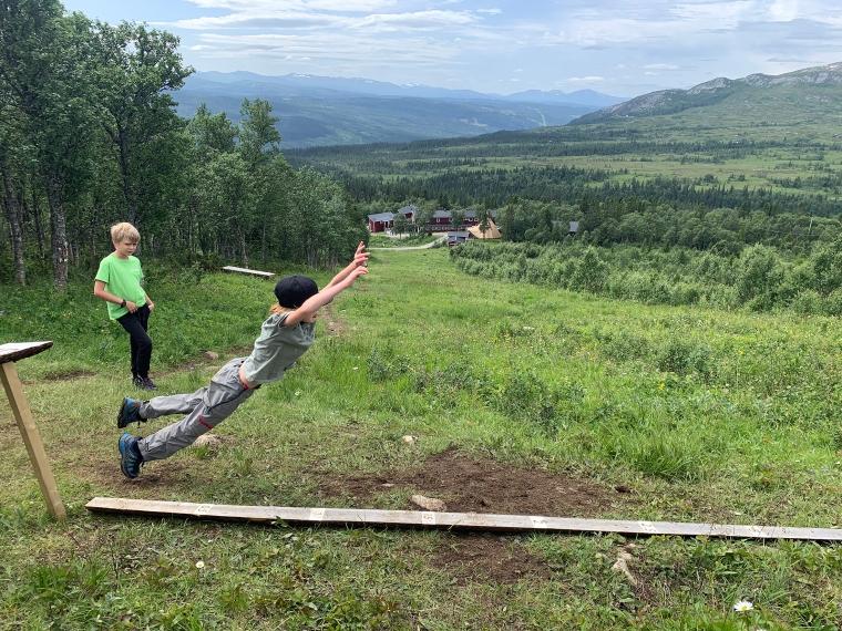 Ett barn hoppar längdhopp längst en planka. Ett annat titar på.