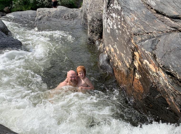 En man och ett barn leker i en forsande vatten.