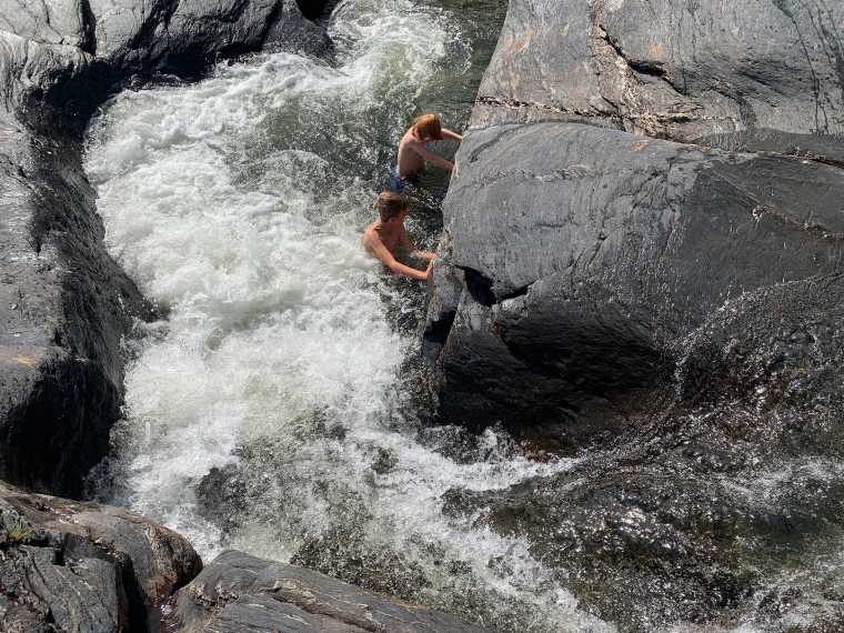 Två barn leker i forsande vatten.